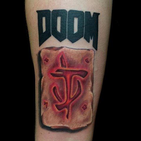 Игровая тату Doom на руке