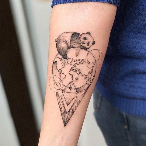 Крутая татуировка панды лежащей на планете Земля